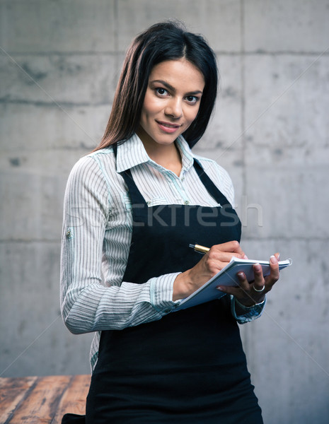 Happy beautiful female waiter in apron Stock photo © deandrobot