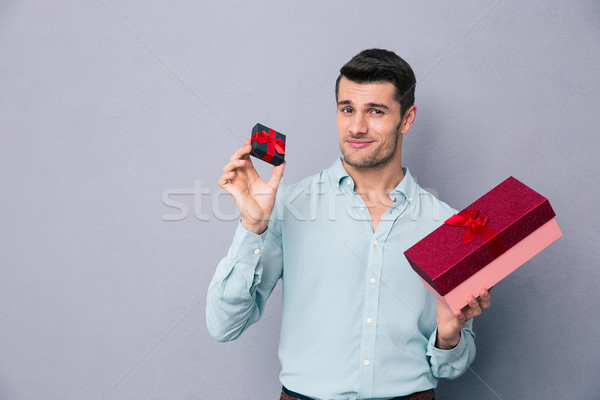 Happy young man holding small and big gift box Stock photo © deandrobot