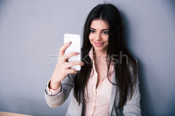 Happy woman selfie photo over gray background Stock photo © deandrobot