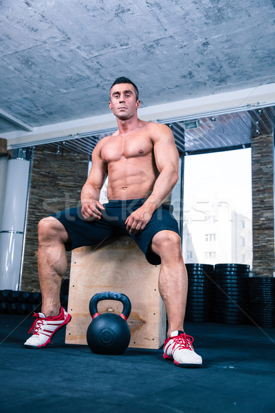 Muscular man sitting on fit box in gym Stock photo © deandrobot