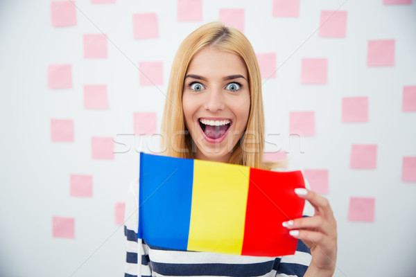 Cheerful woman holding Romanian flag Stock photo © deandrobot