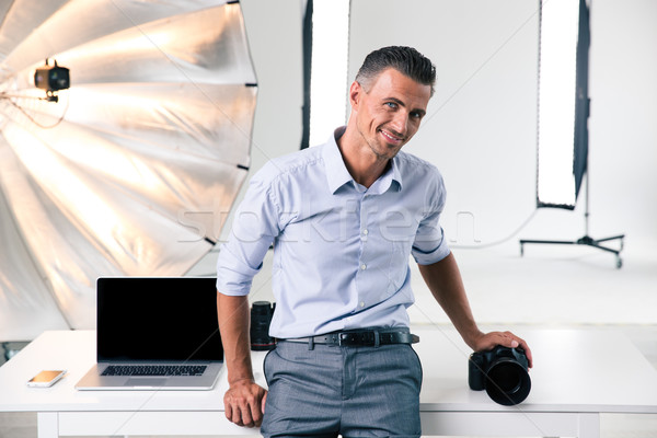 Confident photographer leaning on the table in studi Stock photo © deandrobot