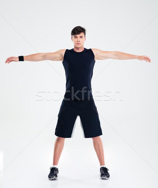 Fitness man doing warm up exercises Stock photo © deandrobot