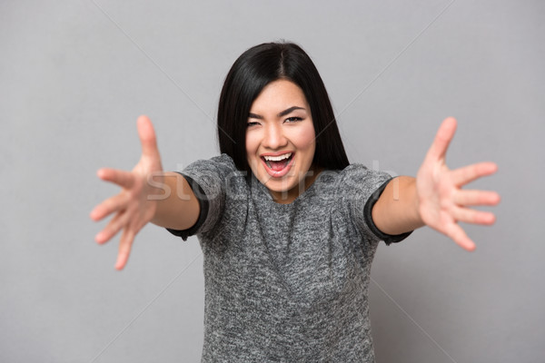 Young woman with an open hand ready for hugging Stock photo © deandrobot