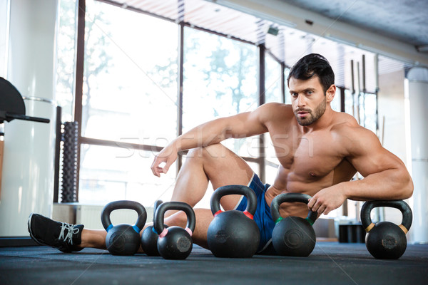 Athletic man sitting near kettle balls Stock photo © deandrobot