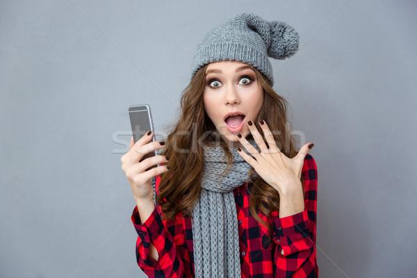 Shocked woman holding smartphone Stock photo © deandrobot