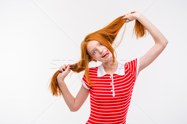 Amusing redhead young woman showing tongue and having fun  Stock photo © deandrobot