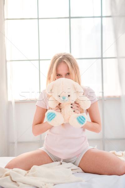 Kobieta posiedzenia miś bed portret młoda kobieta Zdjęcia stock © deandrobot