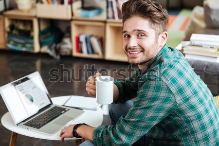 Happy cheerful asian male smiling and using laptop in cafe Stock photo © deandrobot