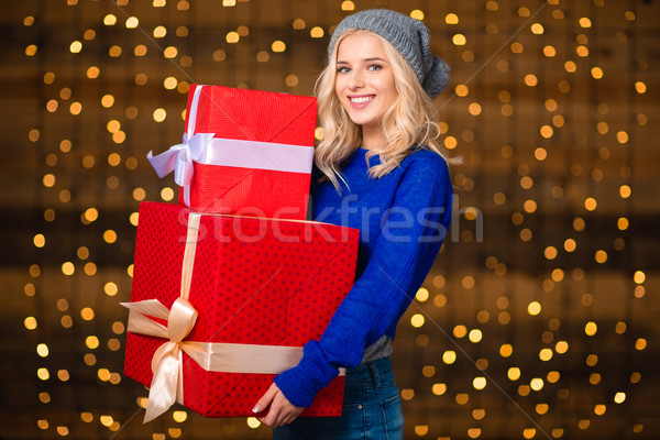 Smiling pretty woman holding gift boxes Stock photo © deandrobot