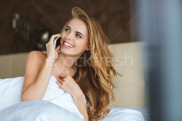 Cheerful happy woman sitting in bed and talking on cellphone Stock photo © deandrobot
