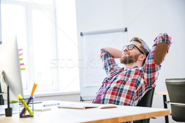 Homme séance mains derrière tête Photo stock © deandrobot