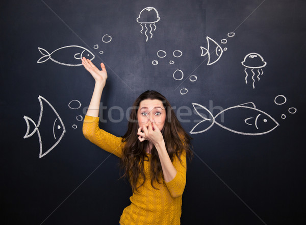 Funny cute woman simulating deep diving over blackboard background Stock photo © deandrobot
