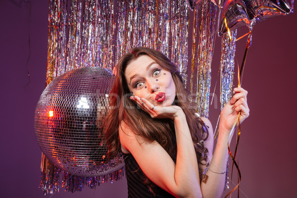 Amusing pretty woman holding balloon and sending a kiss  Stock photo © deandrobot