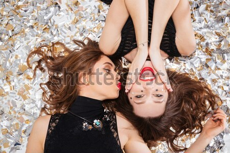 Two seductive beautiful women lying on background of shining confetti Stock photo © deandrobot