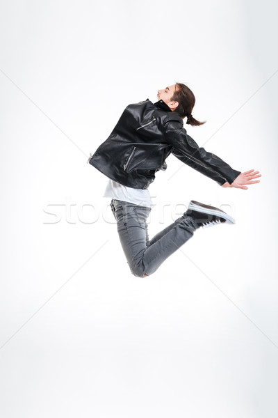 Attractive young man in black leather jacket jumping high Stock photo © deandrobot