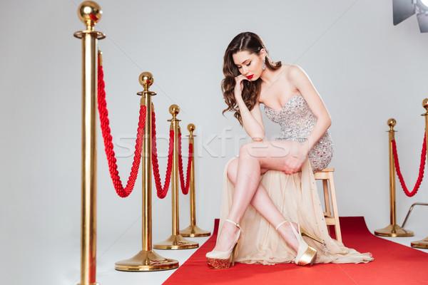 Gyönyörű nő vörös szőnyeg divat ruha ül szék Stock fotó © deandrobot