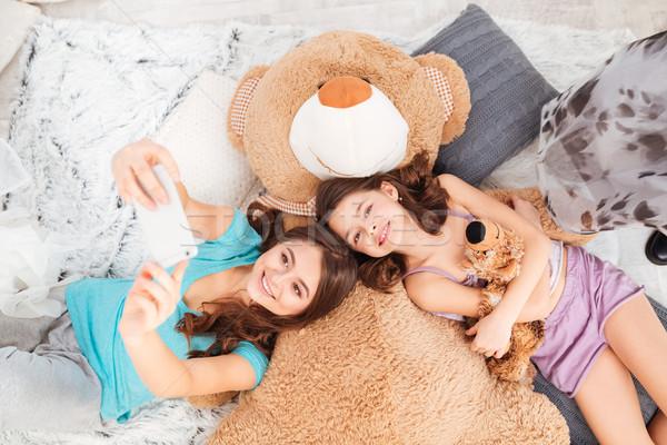 Deux heureux soeurs téléphone portable haut Photo stock © deandrobot