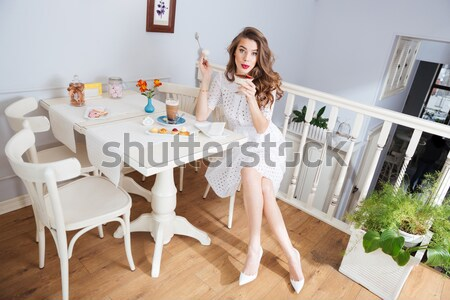 Thoughtful woman standing near window and holding bouquet of flowers Stock photo © deandrobot