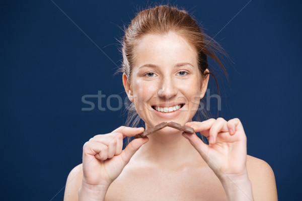 Smiling woman holding chocolate Stock photo © deandrobot