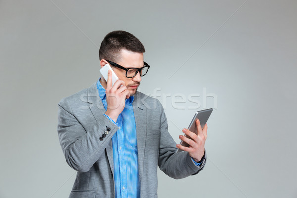 Businessman talking on the phone and using tablet computer Stock photo © deandrobot