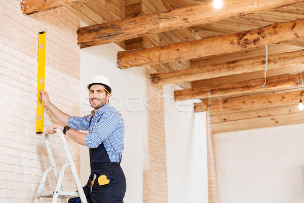Smilling handsome builder using level and standing in the ladder Stock photo © deandrobot