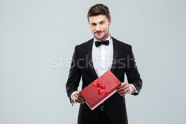 Confident attracive man in tuxedo standing and holding gift box Stock photo © deandrobot