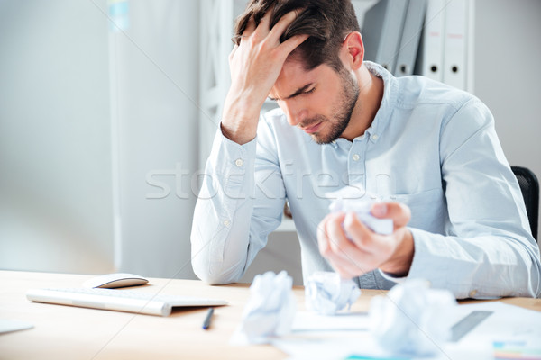 Exhausted stressed young man crumpling paper at workplace Stock photo © deandrobot