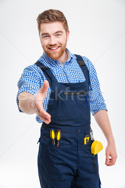 Happy male builder stretching hand for handshake Stock photo © deandrobot