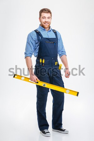 Cheerful handsome young builder in helmet standing and holding drill Stock photo © deandrobot