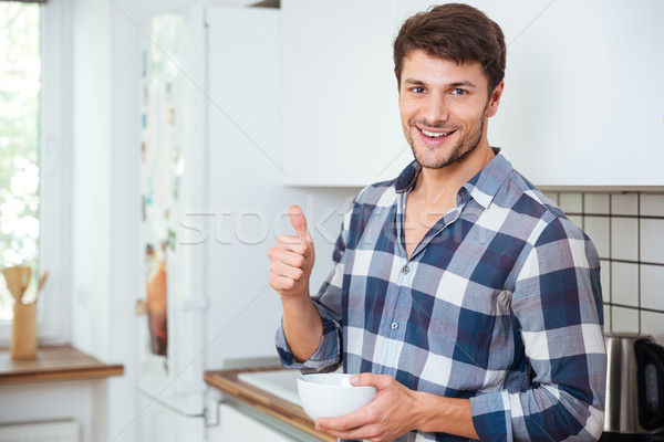 Cheerful young man standing on kitchen and showing thumbs up Stock photo © deandrobot