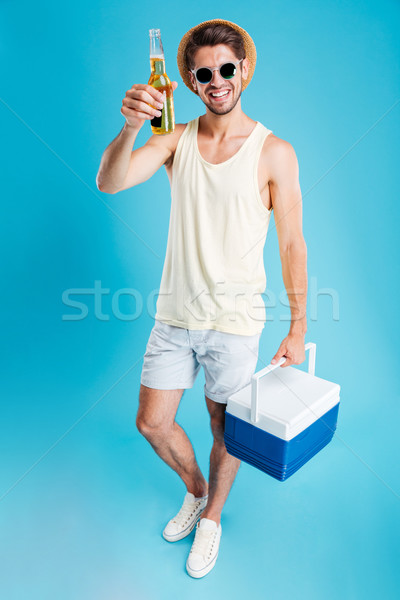 Smiling young man holding cooler bag and drinking beer Stock photo © deandrobot