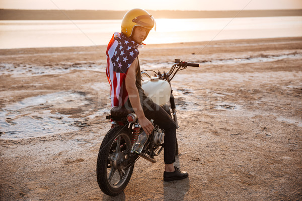 Man in golden in american cape sitting on his motocycle Stock photo © deandrobot