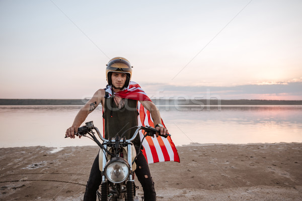 Man in golden helmet and american flag cape driving motorcycle Stock photo © deandrobot