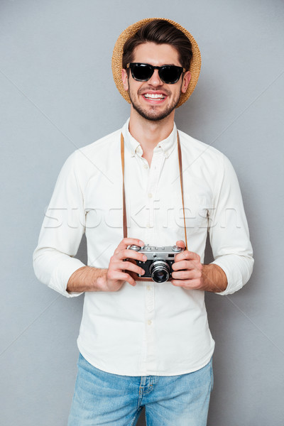 Cheerful young man in hat and sunglasses holding old camera Stock photo © deandrobot