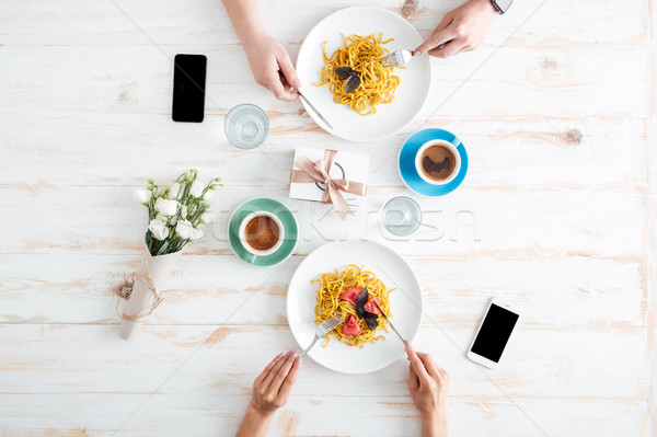 Hands of young couple eating pasta together on wooden table Stock photo © deandrobot