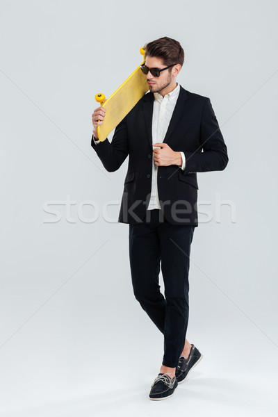 Serious businessman in sunglasses holding yellow skateboard on his sholder Stock photo © deandrobot