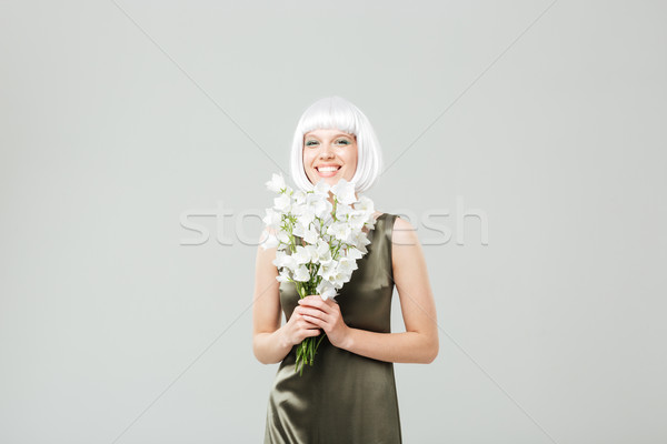 Derűs fiatal nő virágcsokor virágok áll nevet Stock fotó © deandrobot