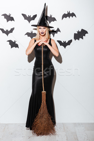 Woman in witch costume with hat standing and holding broom Stock photo © deandrobot