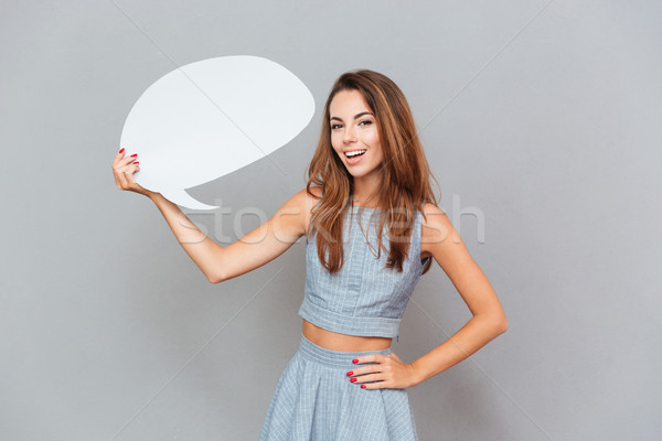 Cheerful attractive young woman standing and holding blank speech bubble Stock photo © deandrobot