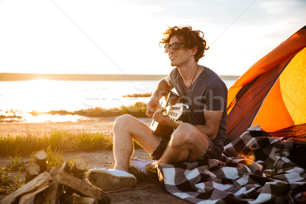 Smiling man sitting near touristic tent and playing guitar Stock photo © deandrobot