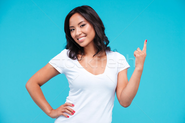 Cheerful young vietnamese girl pointing finger up at copyspace Stock photo © deandrobot