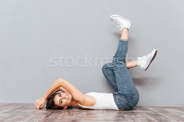 Mosolyog vonzó nő padló kiemelt lábak portré Stock fotó © deandrobot