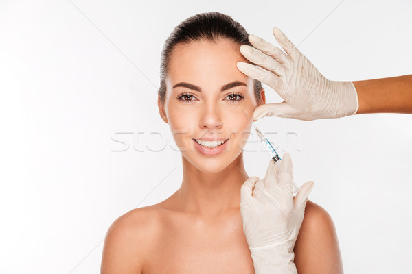 Young woman gets beauty injection in eye area from sergeant Stock photo © deandrobot