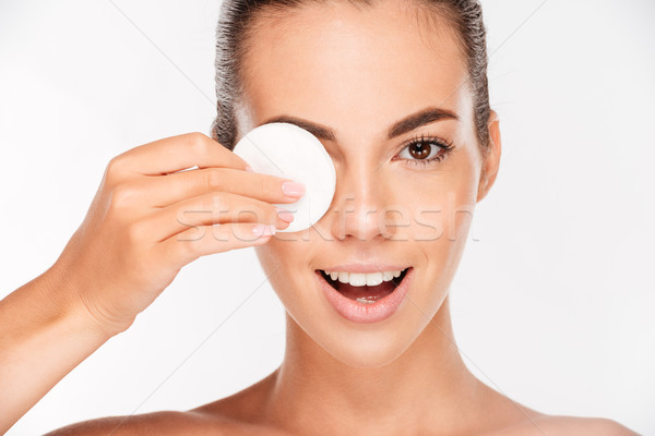 Laughing woman holding round white cotton pad to her eye Stock photo © deandrobot