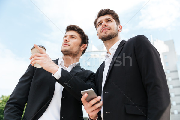 Two businessmen with take away coffee and cell phone outdoors Stock photo © deandrobot