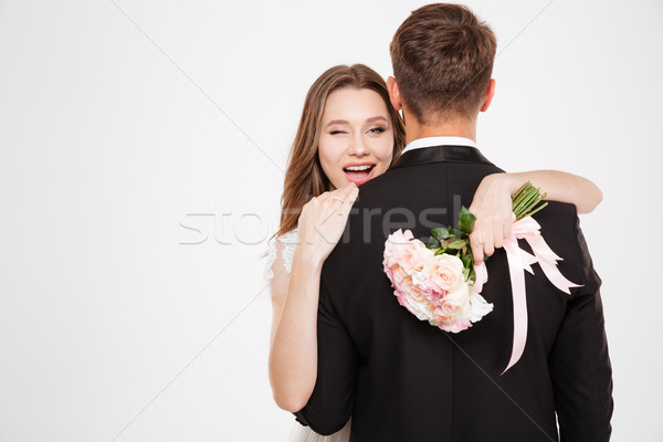 Newlyweds in arms with bouquet Stock photo © deandrobot