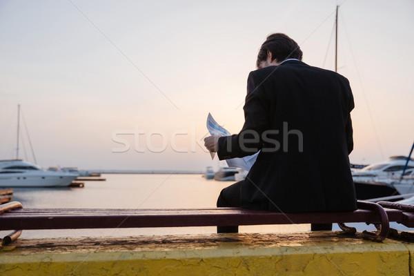 Hátulnézet férfi öltöny újság kikötő ül Stock fotó © deandrobot