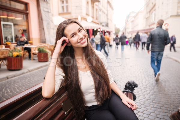 Cheerful young woman sitting on the bench in old town Stock photo © deandrobot