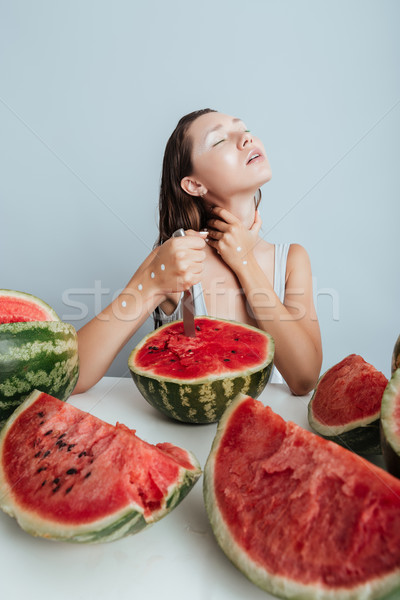 Seductive young woman sitting and cutting watermelon with knife Stock photo © deandrobot